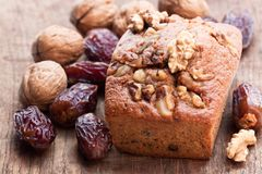 Homemade date and walnut loaf cake on old wooden table stock image
