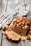 Homemade date and walnut loaf cake on old wooden table stock photography