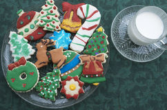 Homemade Decorated Cutout Christmas Cookies On Clear Plate,Green Tablecloth, Glass of Milk Stock Photo