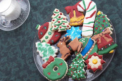 Homemade Decorated Cutout Christmas Cookies On Clear Plate,Green Tablecloth, Glass of Milk Stock Image