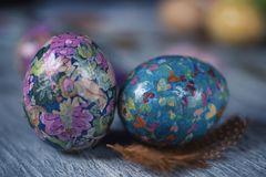 Homemade decorated easter eggs. Closeup of some homemade decorated easter eggs on a gray rustic wooden table sprinkled with feathers of different colors Stock Images