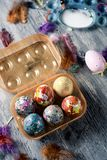 Homemade decorated easter eggs in an egg box. Closeup of some homemade decorated easter eggs in a plastic egg box, and some other easter eggs on a gray rustic Stock Photos