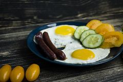 Homemade delicious breakfast with sunny side up fried egg, sausage, tomatos in top view royalty free stock images