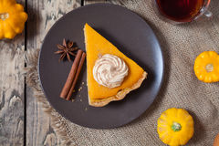 Homemade Delicious Pumpkin Pie made for Thanksgiving, Halloween with whipped cream, spices and autumn decoration Royalty Free Stock Image