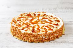 Homemade delicious whole cake with mascarpone cream, white melted chocolate, peanut croquet and caramel icing royalty free stock photography