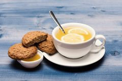 Homemade dessert concept. Sweet bakery and tea time. Cookies near tea on grey wooden background. Oatmeal biscuits as tasty pastry for cup of tea with lemon and royalty free stock photo