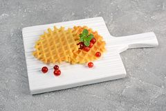 Homemade dessert. Sweet waffles with cranberry and mint on white wooden cutting board. On gray concrete background Stock Photo