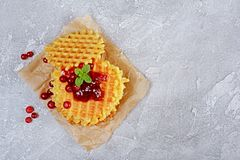 Homemade dessert. Sweet waffles with fresh cranberry, jam and mint on parchment paper. On gray concrete background Stock Photo