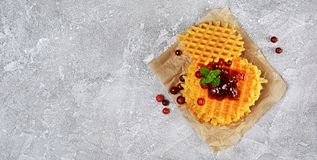 Homemade dessert. Sweet waffles with fresh cranberry, jam and mint on parchment paper. On gray concrete background Stock Images