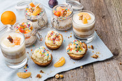 Homemade desserts - biscuits with yogurt, tangerines and walnuts in glass, oats with fresh fruit in glass jar and Royalty Free Stock Photography