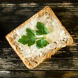Homemade dietetic tasty sandwich with butter and parsley for breakfast. On dark rustic wooden background. Top view. Square. Close-up royalty free stock images