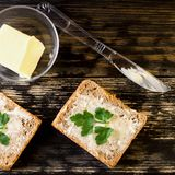 Homemade dietetic tasty sandwiches with butter and parsley for b. Reakfast. On dark rustic wooden background. Top view. Square. Close-up stock image