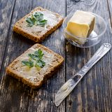 Homemade dietetic tasty sandwiches with butter and parsley for b. Reakfast. On dark rustic wooden background. Square. Close-up stock photo