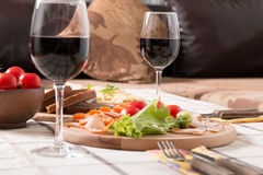 Homemade dinner with bread, tomatoes, cheese, ham and wine. On the table Royalty Free Stock Image