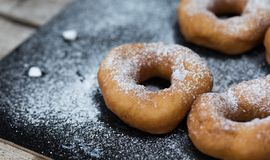 Homemade donuts with icing sugar powder on wooden background royalty free stock photos