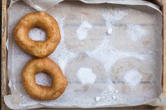 Homemade donuts with icing sugar powder on wooden background stock images