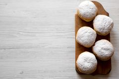 Homemade donuts with jelly and powdered sugar on rustic wooden board over white wooden table, top view. Copy space stock images