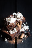Homemade Double Chocolate Cake with Crushed Meringues and Wafer Rolls. Dark Wooden Table Background. Moody Atmosphere Royalty Free Stock Photography