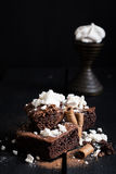 Homemade Double Chocolate Cake with Crushed Meringues and Wafer Rolls. Dark Wooden Table Background. Moody Atmosphere Royalty Free Stock Photos