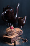 Homemade Double Chocolate Cake with a Ripe Berry on Top. Ceramic Wine Jug and a Cup in the Background. Moody Atmosphere Stock Photography