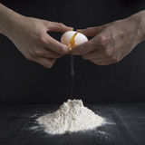 Homemade dough. Hands woman break an egg into the flour to the dough Royalty Free Stock Image