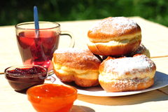 Homemade doughnuts with jam filling & a cup of tea Stock Photo
