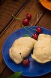 Homemade dumplings with cherries. Wooden background. Top view. Close-up. Homemade dumplings with cherries. Wooden background. Close-up. Top view Stock Photography