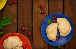 Homemade dumplings with cherries. Wooden background. Top view. Close-up Stock Photography