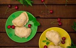 Homemade dumplings with cherries. Wooden background. Top view. Close-up. Homemade dumplings with cherries. Wooden background. Close-up. Top view Stock Photos