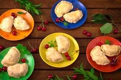 Homemade dumplings with cherries. Wooden background. Top view. Close-up. Homemade dumplings with cherries. Wooden background. Close-up. Top view Stock Photo