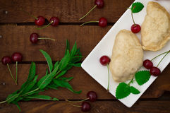 Homemade dumplings with cherries. Wooden rustic background. Close-up. Top view Royalty Free Stock Image