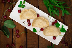 Homemade dumplings with cherries. Wooden rustic background. Close-up. Top view Stock Photography