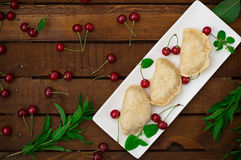 Homemade dumplings with cherries. Wooden rustic background. Close-up. Top view Stock Image
