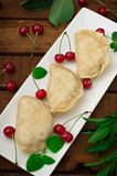 Homemade dumplings with cherries. Wooden rustic background. Close-up. Top view Royalty Free Stock Photo