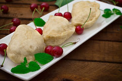 Homemade dumplings with cherries. Wooden rustic background. Close-up. Top view Royalty Free Stock Photos