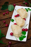 Homemade dumplings with cherries. Wooden rustic background. Close-up. Top view Royalty Free Stock Images