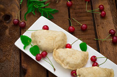 Homemade dumplings with cherries. Wooden rustic background. Close-up. Top view Stock Photo