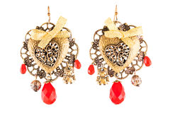 Homemade earrings with red stones and golden bows Royalty Free Stock Photography