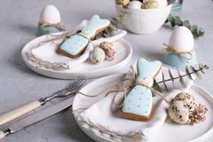 Homemade easter cookies in the shape of  a  funny  rabbit  on white plate. Easter  festive table setting. Holiday decorations Royalty Free Stock Images
