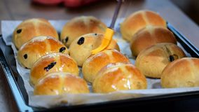 Homemade Easter traditional hot cross buns. Female hands cover with syrup. HD stock video footage