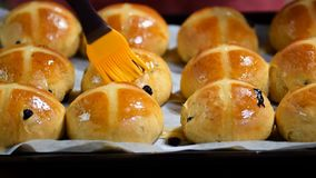 Homemade Easter traditional hot cross buns. Female hands cover with syrup. HD stock video