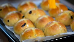 Homemade Easter traditional hot cross buns. Female hands cover with syrup. Homemade Easter traditional hot cross buns. Female hands cover with syrup stock footage