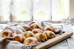 Hot cross buns. Homemade Easter traditional hot cross buns on wooden tray with textile over white wooden table. Window at background. Natural day light. Rustic Royalty Free Stock Photo