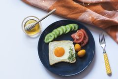 Homemade egg in a hole with toast bread and colorful vegetables on a blue ceramic plate on white table with yellow fork stock image