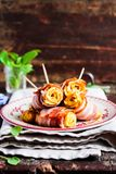 Homemade egg omelette rolls  with spinach wrapped in roasted bacon slices. Stacked on a plate, selective focus Royalty Free Stock Photography