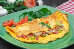 Homemade egg omlette for breakfast. Omlet garnished with tomato and rucola salad stock photos