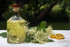 Homemade elderflower syrup in a glass bottle, elderflower umbel. And lemon slices on a white wooden table in the garden, refreshing drink in summer, selective royalty free stock image