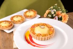 Homemade exotic tart - passion fruit ganache, lime curd, exotic marmalade, coconut biscuits royalty free stock photos