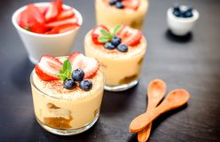 Homemade, exquisite dessert tiramisu in glasses decorated with strawberry, blueberry, mint on black wooden table. Tiramisu, traditional Italian dessert in glass stock photography