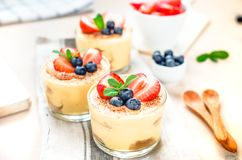 Homemade, exquisite dessert tiramisu in glasses decorated with strawberry, blueberry, mint on white wooden table royalty free stock photos